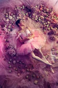 Vista superior de la hermosa joven en tutú de ballet rosa rodeada de flores