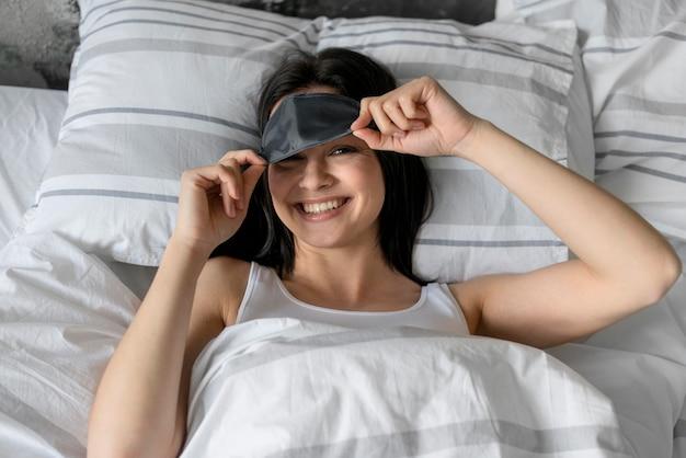 Vista superior hermosa mujer con antifaz para dormir