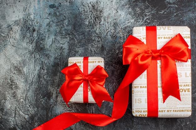 Vista superior de hermosas cajas de regalo atadas con cinta roja en diferentes tamaños sobre fondo oscuro helado