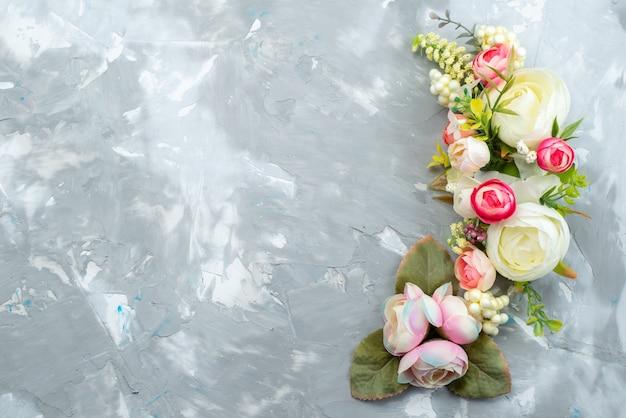 Una vista superior de hermosas flores con hojas en un escritorio brillante, color de plantas de flores
