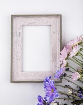 Vista superior de hermosas flores de margarita rosa pálido y violeta sobre un fondo blanco con espacio de copia