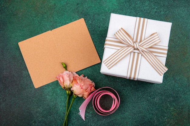 Vista superior de hermosas flores rosadas con cinta rosa con caja de regalo en gre con espacio de copia
