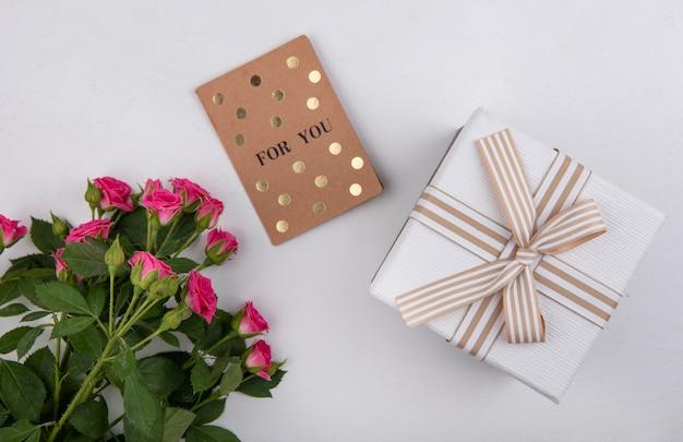 Vista superior de hermosas rosas rosadas con hojas y caja de regalo blanca sobre un fondo blanco.