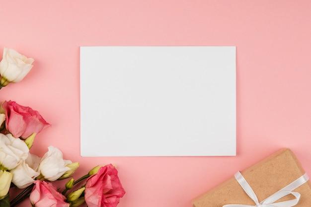 Vista superior hermoso arreglo de rosas con tarjeta vacía y regalo