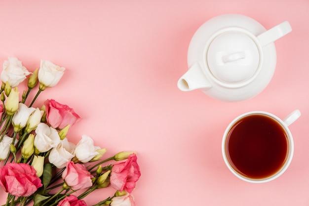 Vista superior hermoso arreglo de rosas con tetera y taza de té