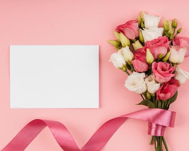 Vista superior hermoso ramo de rosas con tarjeta vacía