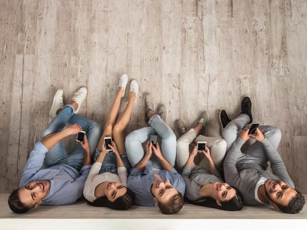 Vista superior de hermosos jóvenes están utilizando teléfonos inteligentes.