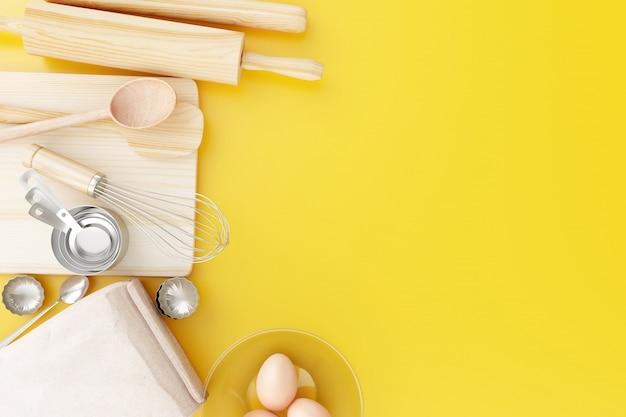 Vista superior herramientas para hornear sobre fondo amarillo.