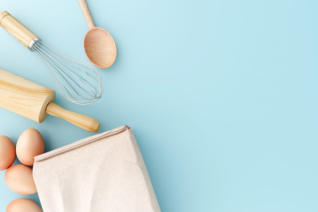 Vista superior herramientas para hornear sobre fondo azul pastel.