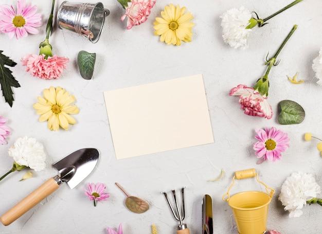 Vista superior de herramientas de jardinería y plantas con papel vacío