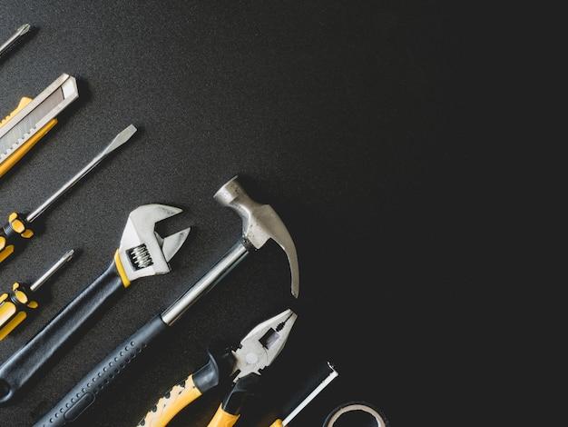 Vista superior de herramientas mecánicas en fondo negro con espacio de copia.