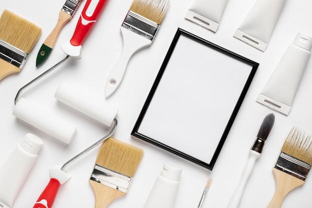 Vista superior con herramientas de pintura y marco