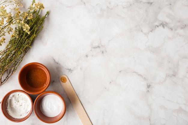 Vista superior de hierbas y crema en la mesa