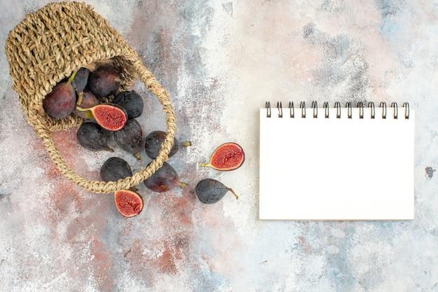 Vista superior de higos frescos esparcidos de la canasta de un cuaderno sobre fondo desnudo