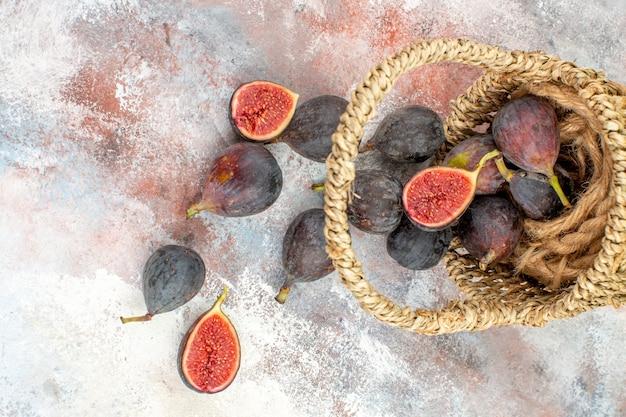 Vista superior de higos frescos esparcidos de la canasta sobre fondo desnudo