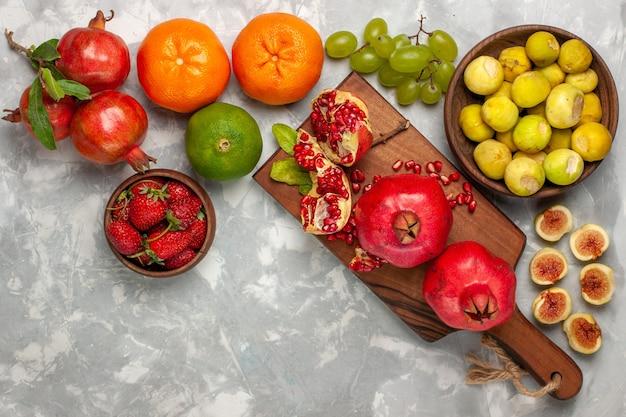 Vista superior de higos frescos con granadas y uvas en el escritorio blanco