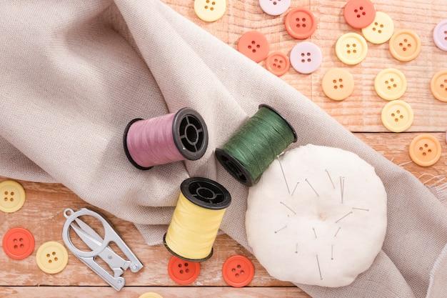 Vista superior del hilo de coser con botones y tela