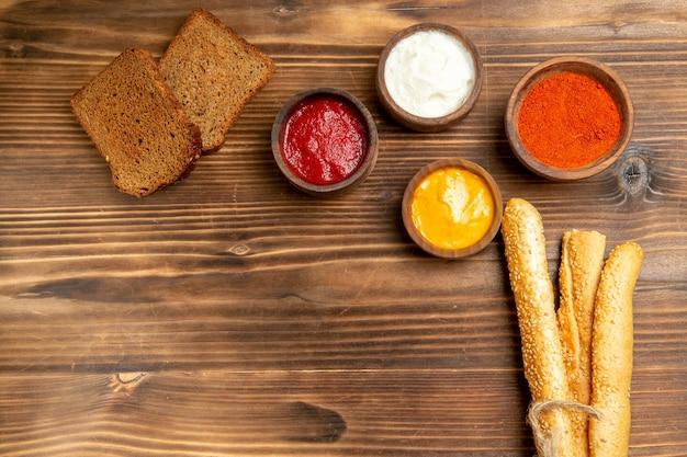 Vista superior de hogazas de pan oscuro con bollos y condimentos en la mesa de madera marrón comida pan bollo condimento
