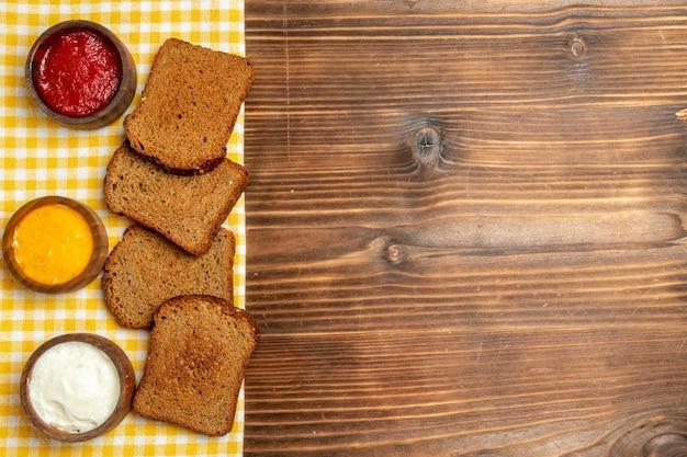 Vista superior de hogazas de pan oscuro con condimentos en el condimento picante de pan de mesa de madera marrón