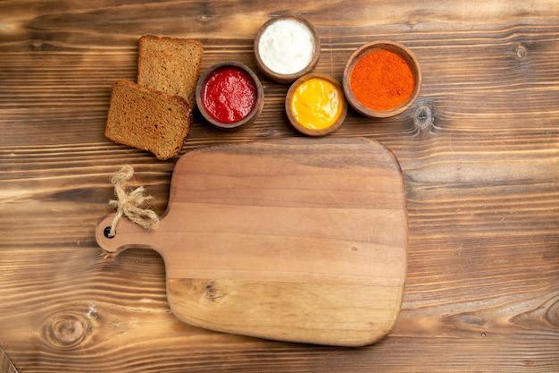 Vista superior de hogazas de pan oscuro con condimentos en la mesa de madera marrón comida pan bollo condimento comida