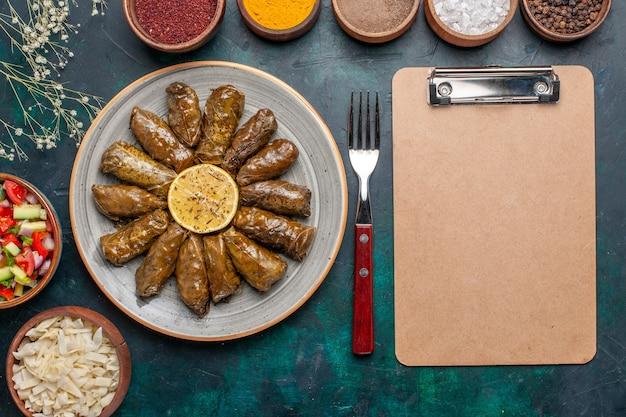 Vista superior de la hoja dolma deliciosa comida de carne oriental enrollada dentro de hojas verdes con condimentos y verduras en rodajas en el escritorio azul cena de carne plato de salud