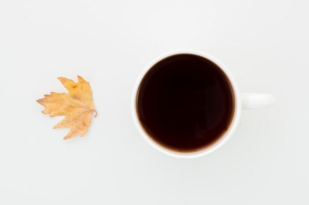 Vista superior hoja de otoño con café