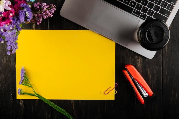 Vista superior de la hoja de papel amarillo con clips de papel de colores con flores de color púrpura statice y portátil con una taza de café engrapadora roja sobre fondo de madera oscura