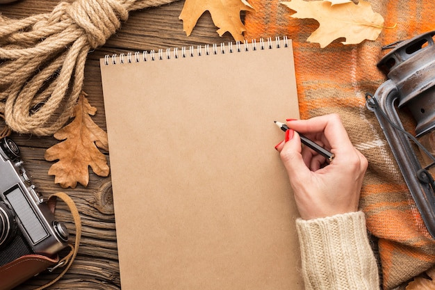 Vista superior de hojas con cuaderno y cámara