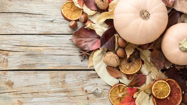 Vista superior de hojas de otoño con cítricos secos y calabaza
