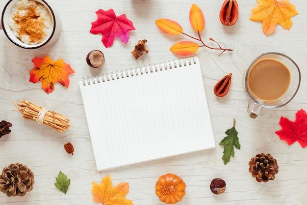 Vista superior de las hojas de otoño con un cuaderno.