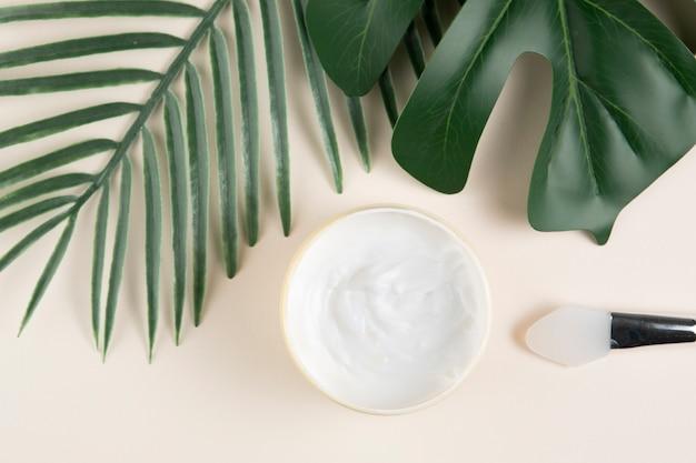 Vista superior de hojas tropicales y cosméticos corporales.