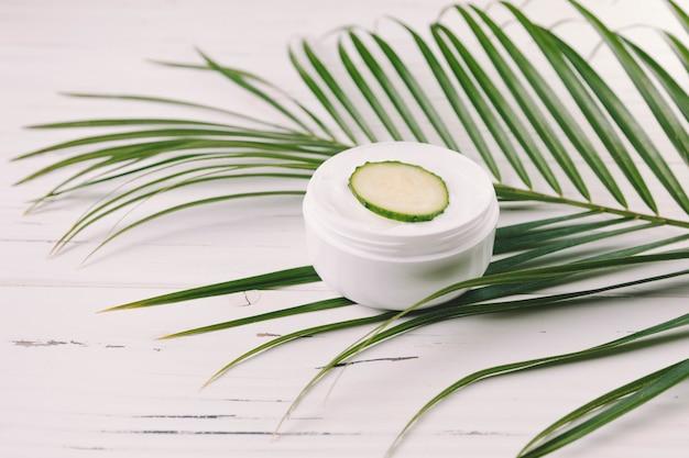 Vista superior hojas tropicales con herramientas de belleza y cosméticos