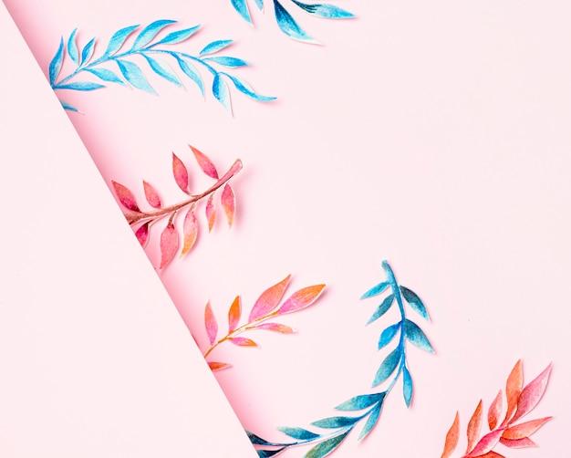 Vista superior de hojas tropicales sobre fondo rosa