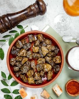 Vista superior de hojas de uva azerbaiyana dolma en cacerola de cerámica servido con yogur