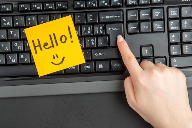 Vista superior hola escrito en papel de nota mano femenina en el teclado en la tecla enter sobre fondo oscuro