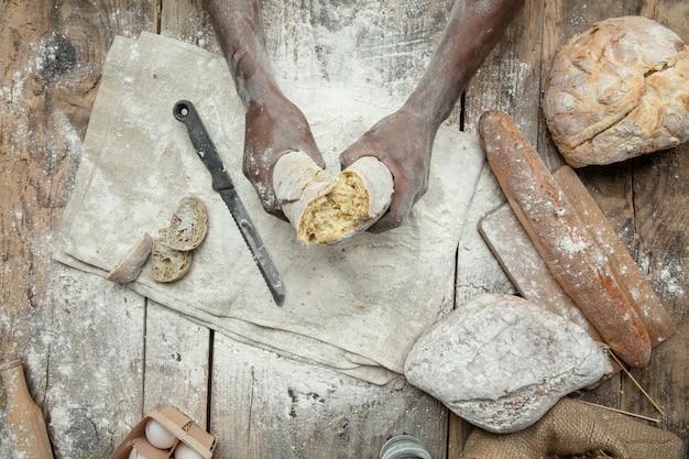 Vista superior del hombre afroamericano cocina cereal fresco, pan, salvado en la mesa de madera