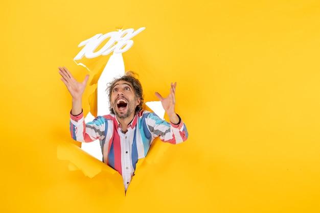 Vista superior del hombre barbudo sonriente jugando con diez números porcentuales en un agujero rasgado en papel amarillo