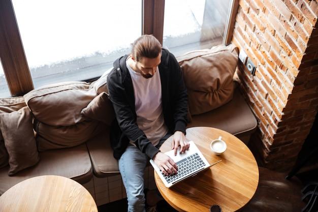 Vista superior del hombre barbudo usando laptop en café