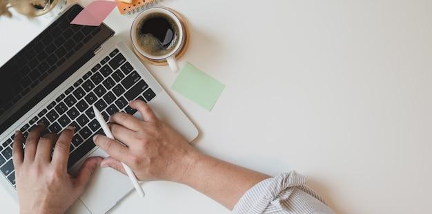 Vista superior del hombre escribiendo en la computadora portátil en un lugar de trabajo mínimo