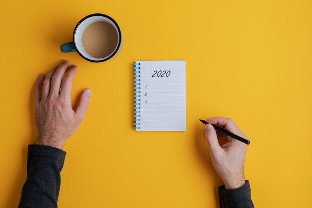 Vista superior de un hombre escribiendo planes o resoluciones para el año 2020