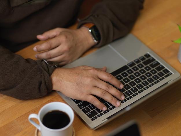 Vista superior del hombre escribiendo en el teclado de la computadora portátil en la mesa de madera con taza de café
