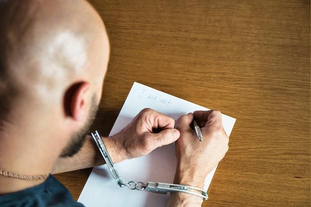 Vista superior de un hombre esposado escribiendo en un papel