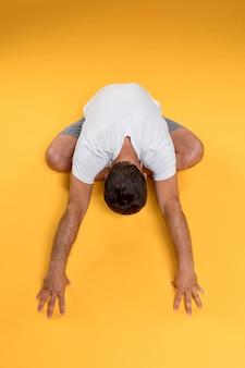 Vista superior hombre estiramiento en pose de yoga