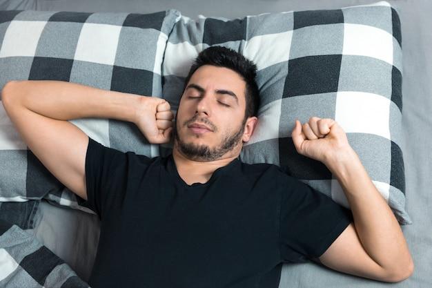 La vista superior del hombre guapo bosteza y se frota los ojos mientras duerme en la cama.