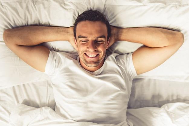 Vista superior del hombre guapo sonriendo mientras está acostado.