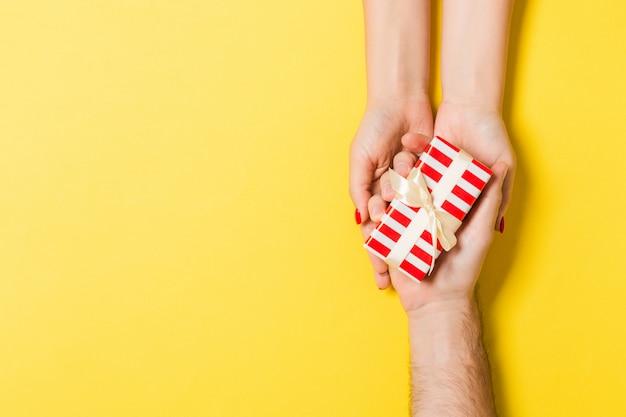 Vista superior de un hombre y una mujer felicitándose con un regalo. sorpresa para un concepto de vacaciones. de cerca
