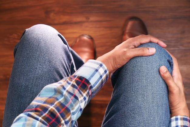 Vista superior del hombre que sufre dolor en las articulaciones de la rodilla sentado en una silla