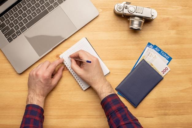 Vista superior del hombre que trabaja en el escritorio haciendo planes de viaje o vacaciones