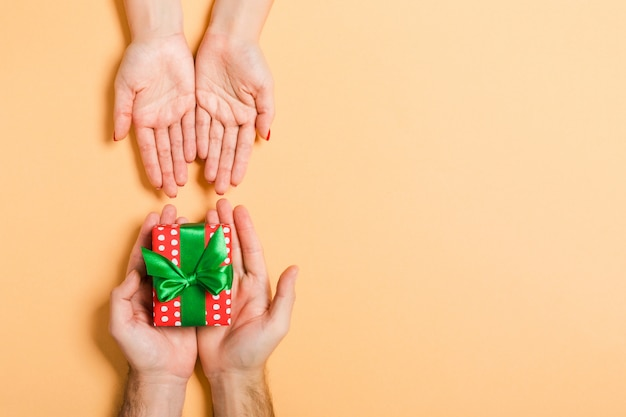 Vista superior de un hombre sosteniendo y dando un regalo a una mujer. recibiendo un regalo. cerca del concepto de vacaciones
