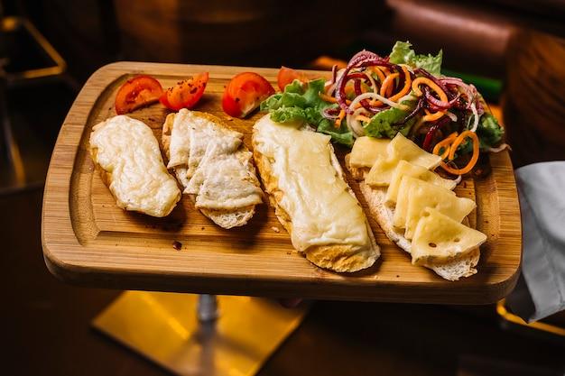 Vista superior, un hombre sostiene una bandeja con tostadas de queso con rodajas de tomate y ensalada de verduras
